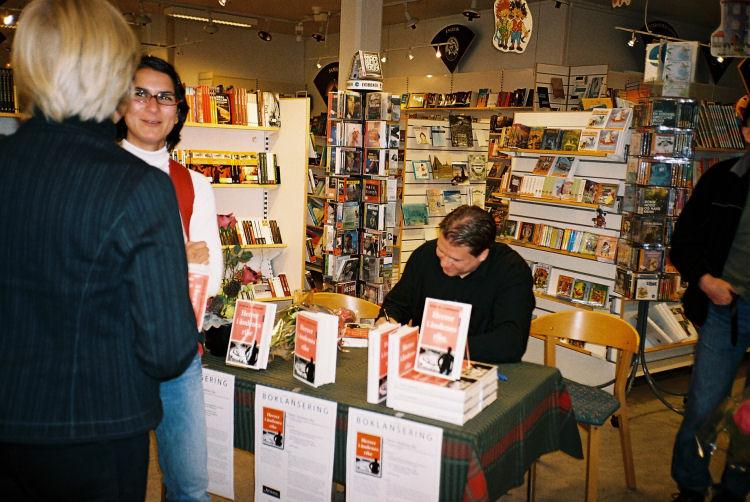 Forfatteren signerer bøker mens universitetslektorene Mariann Solberg (med ryggen til) og Rani Lill Anjum fra Filosofisk institutt prater sammen.